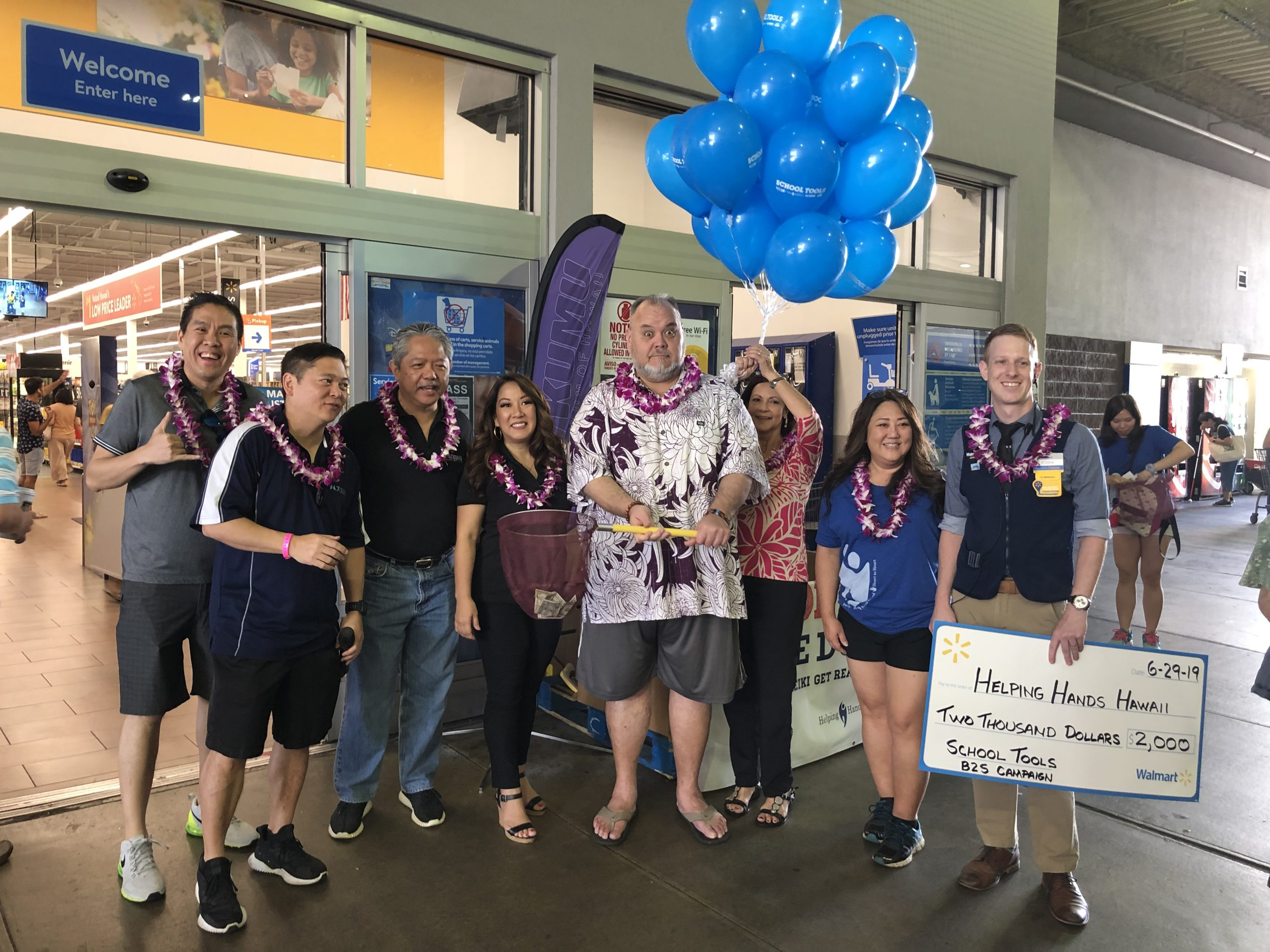 People pose in front of a store entrance during a donation drive for Helping Hands Hawaii.